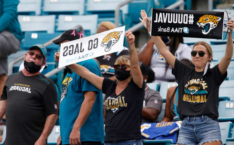 a group of people holding a sign: Jacksonville Jaguars fans cheer during the second half against the Indianapolis Colts at TIAA Bank Field.