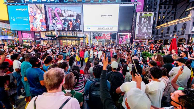 a group of people walking down the street in front of a crowd: Times Square, New York City