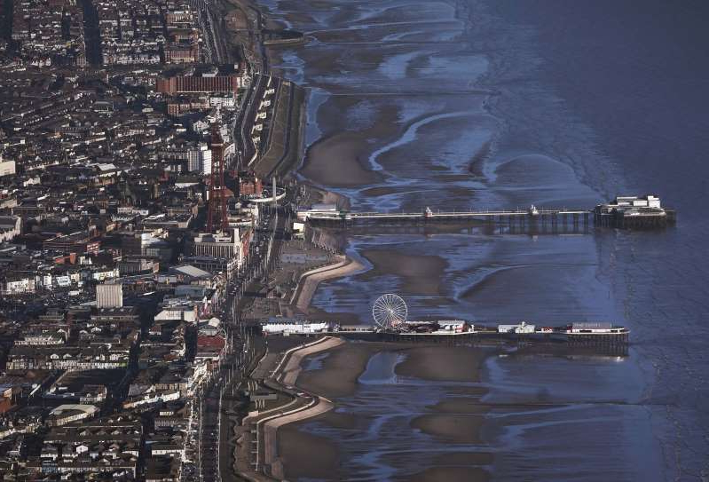 a large body of water: Blackpool bathed in sunlight as seen from the air (Owen Humphreys/PA)