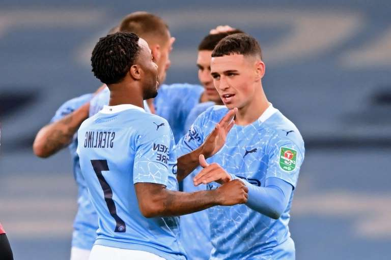 a man holding a football ball: Phil Foden (left)scored the winner as Manchester City remained in contention for a fourth straight League Cup
