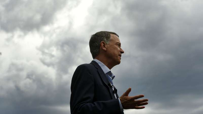 a man standing in front of a cloudy sky: Former Colorado Gov. John Hickenlooper speaks to members of the media in front of the state Capitol on August 4, 2019, in Denver.