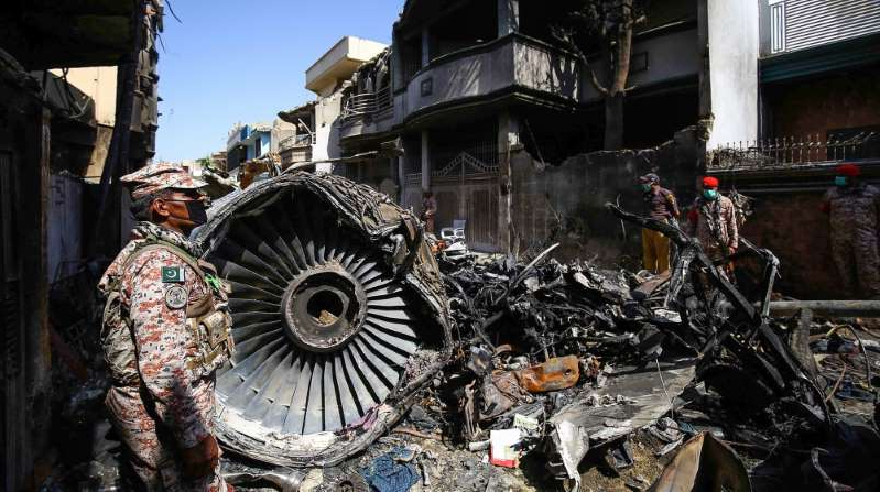 a motorcycle parked on the side of a building: A Pakistan International Airlines Airbus A320 crashed into a residential area of Karachi, Pakistan, on May 24, killing 98 people [File: Shahzaib Akber/EPA]