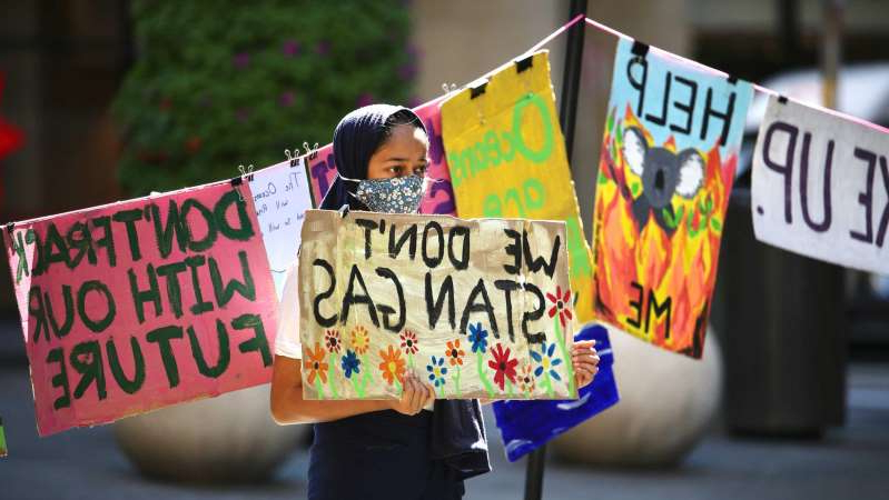 a person holding a sign: At the Sydney strike, placards were strung across washing lines to represent the students who could not attend due to COVID-19 restrictions. (ABC News: James Carmody)