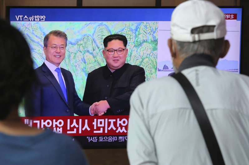 Kim Jong-un, Moon Jae-in standing in front of a screen