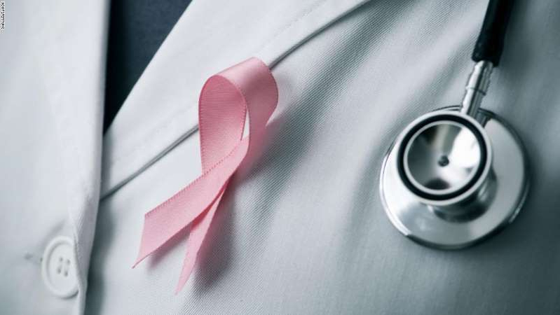 a close up of a knife: closeup of a young caucasian doctor man with a pink ribbon for the breast cancer awareness pinned in the flap of his white coat; Shutterstock ID 724387357; Job: CNN Digital