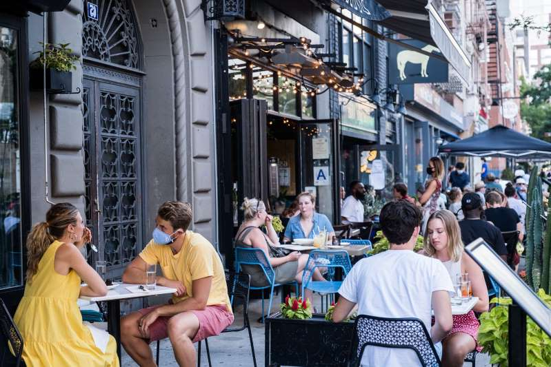 a group of people walking on a city street: NEW YORK, NY - JULY 21: People dine al fresco, or open air, in the East Village on July 21, 2020 in New York City. New York City's Open Restaurant Program, which seeks to phase in city-side options to expand outdoor seating for food establishments, has been extended through October. (Photo by Jeenah Moon/Getty Images)