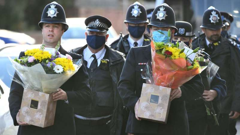 a group of people wearing costumes: Met officers carry flowers to place at the scene in south London
