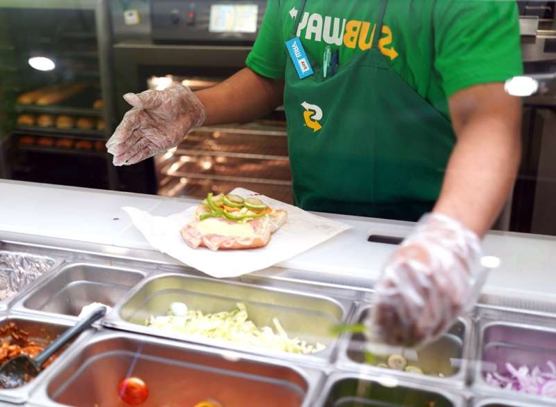 a person sitting at a table with a plate of food: Subway sandwich artist making sub