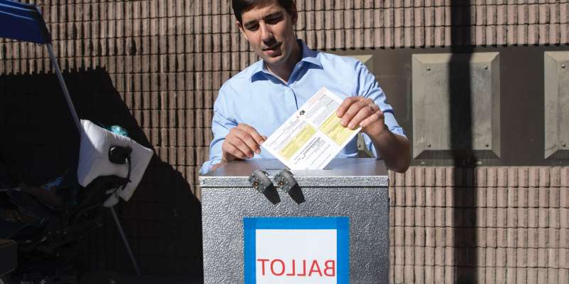 a person sitting in front of a building: Democratic candidate for California's 10th Congressional District Josh Harder places his ballot inside a ballot box at a polling station on November 6, 2018 in Modesto, California. Alex Edelman/Getty Images