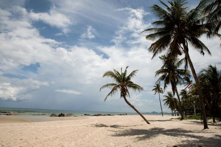 a sandy beach next to a palm tree: Thailand's tourism sector has been hammered by the coronavirus pandemic, but some domestic tourism is still happening because of relatively low infections within its borders