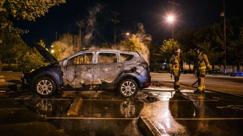 a car parked on a rainy night: Firefighters stand next to a burned out car, Sept. 26, 2020, in Louisville, Kentucky.