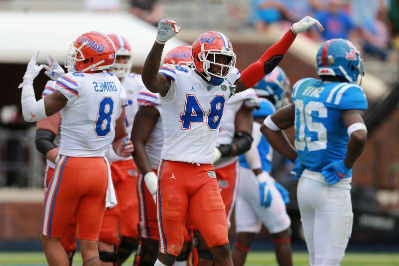 a group of baseball players standing on top of a field: Florida receiver Kyle Pitts celebrates his fourth touchdown of the day against Mississippi.