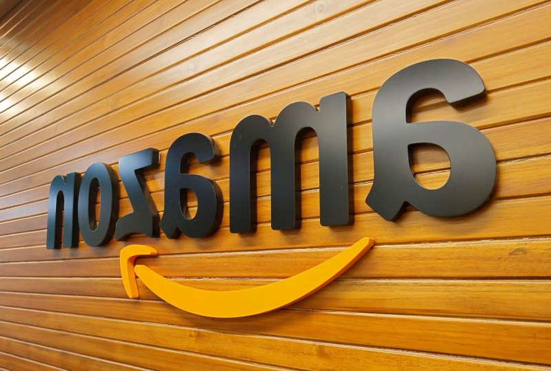 a sign on a wooden surface: FILE PHOTO: The logo of Amazon is pictured inside the company's office in Bengaluru