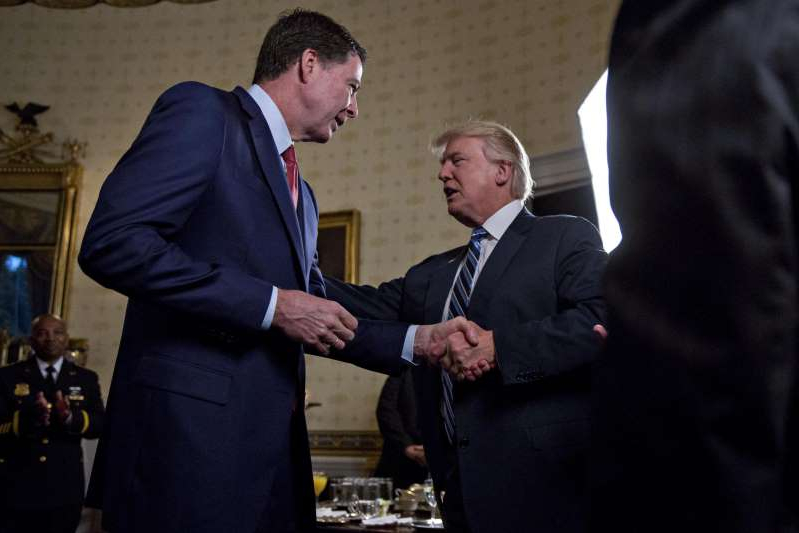 Donald Trump wearing a suit and tie: U.S. President Donald Trump (C) shakes hands with James Comey, director of the Federal Bureau of Investigation (FBI), during an Inaugural Law Enforcement Officers and First Responders Reception in the Blue Room of the White House on January 22, 2017 in Washington, DC.