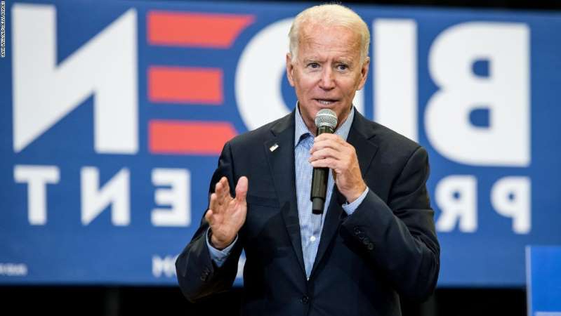 Joe Biden wearing a suit and tie and holding a sign: Democratic presidential candidate and former US Vice President Joe Biden addresses a crowd at a town hall event at Clinton College on August 29, 2019 in Rock Hill, South Carolina. (Photo by Sean Rayford/Getty Images)
