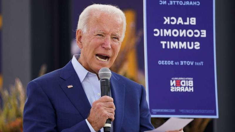 Joe Biden wearing a suit and tie: Democratic presidential nominee Joe Biden speaks at an outdoor