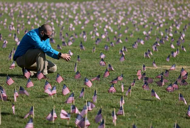 Slide 1 of 4: Chris Duncan, whose 75-year-old mother Constance died from COVID-19 on her birthday, photographs a COVID Memorial Project installation of 20,000 American flags on the National Mall as the United States crosses the 200,000 lives lost in the COVID-19 pandemic Sept. 22, 2020 in Washington, DC. The flags are displayed on the grounds of the Washington Monument facing the White House.