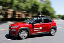 a car driving on a road: An autonomous vehicle demonstrates delivery of medical supplies during the COVID-19 outbreak in California, but critics say don't hold your breath that a driverless car will pull up in front of your Canadian home any time soon.
