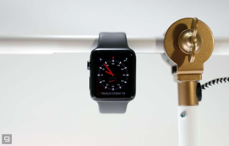 a clock that is on the phone: Apple Watch Series 3 hanging off a bar