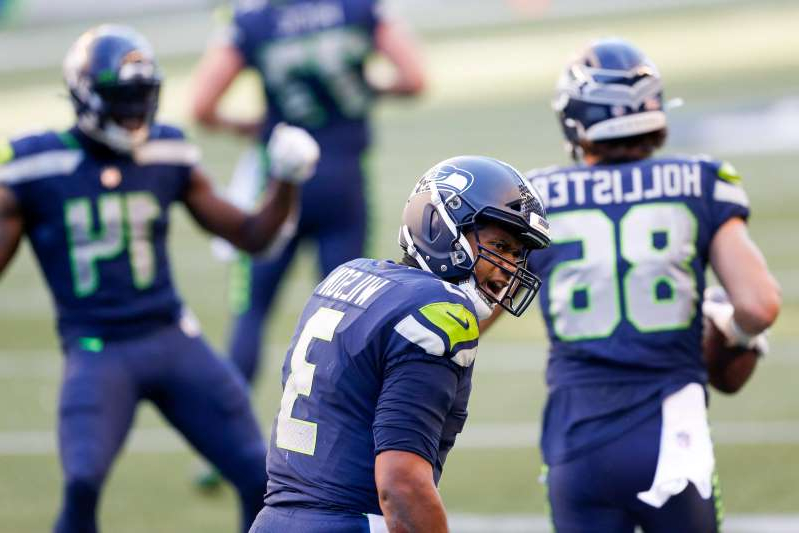 a group of baseball players standing on top of a field: Seattle Seahawks quarterback Russell Wilson (3) celebrates after converting a two point attempt against the Dallas Cowboys during the fourth quarter at CenturyLink Field.