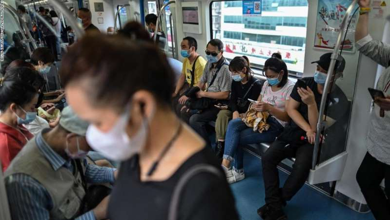 a group of people in a room: Passengers ride the subway in Wuhan, in China's central Hubei province on September 28, 2020. The city where cases of the coronavirus were first detected has largely returned to normal.