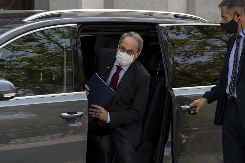 a man wearing a suit and tie talking on a cell phone: Joaquim Torra leaves a Supreme Court session in Madrid on Sept. 17.