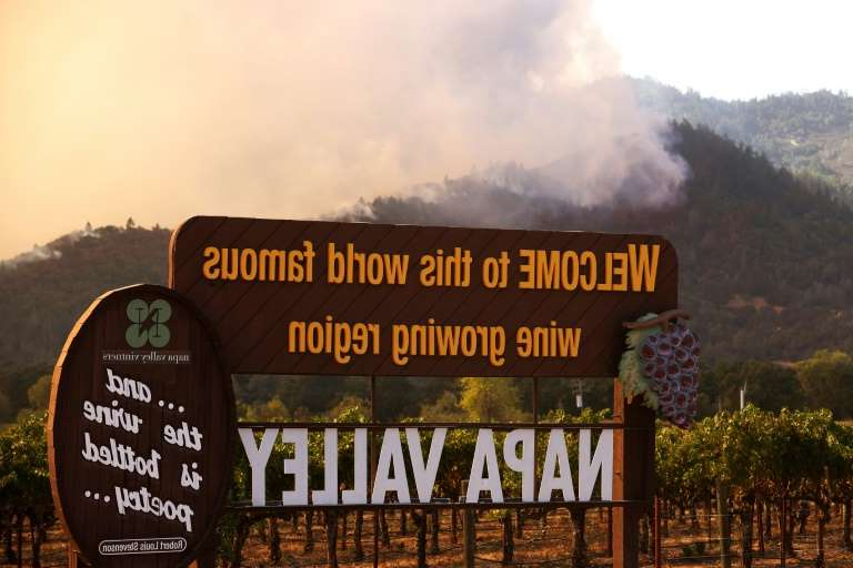 a sign with a mountain in the background: Wildfire rips through the world-famous Napa Valley, with smoke rising from the fast-moving Glass Fire on hills on September 27, 2020 in Calistoga, California