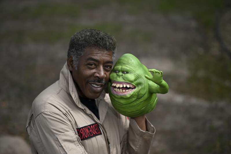Ernie Hudson wearing a green shirt: ROBBINSDALE, MN - MAY 5: Ghostbusters co-star Ernie Hudson poses for a portrait after recording an uplifting video message for a fan in his backyard Tuesday while donning his Ghostbusters jumpsuit and a