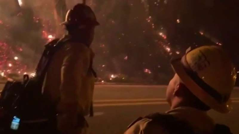 a group of people riding on the back of a man: Jeff Paul reports the latest on the California wildfires and if there is hope on the horizon