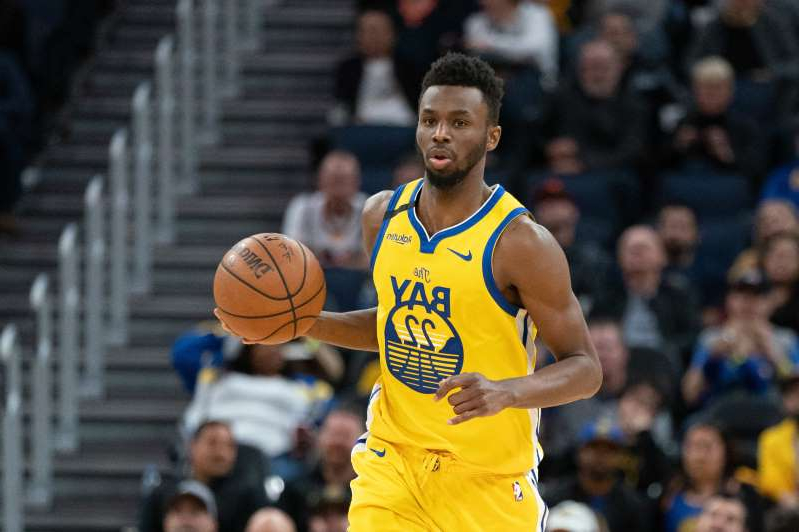 Andrew Wiggins standing in front of a crowd of people watching a football game: Golden State Warriors guard Andrew Wiggins is rooting for former Timberwolves teammate Jimmy Butler and the Heat in the NBA Finals.