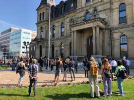a group of people walking in front of a building: Crowd gathered in front of N.B. legislature to protest the province's lack of funding for abortions outside of hospitals.