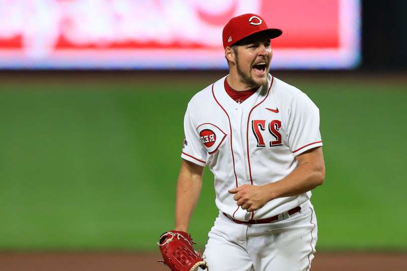 a man in a baseball uniform throwing a ball: Cincinnati Reds' Trevor Bauer reacts after recording a strikeout against Milwaukee Brewers' Christian Yelich last week.