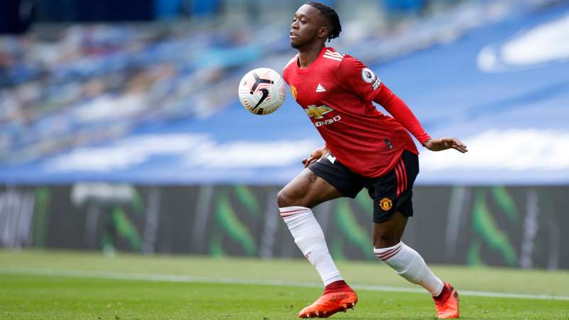 a man with a football ball on a field: Manchester United full-back Aaron Wan-Bissaka