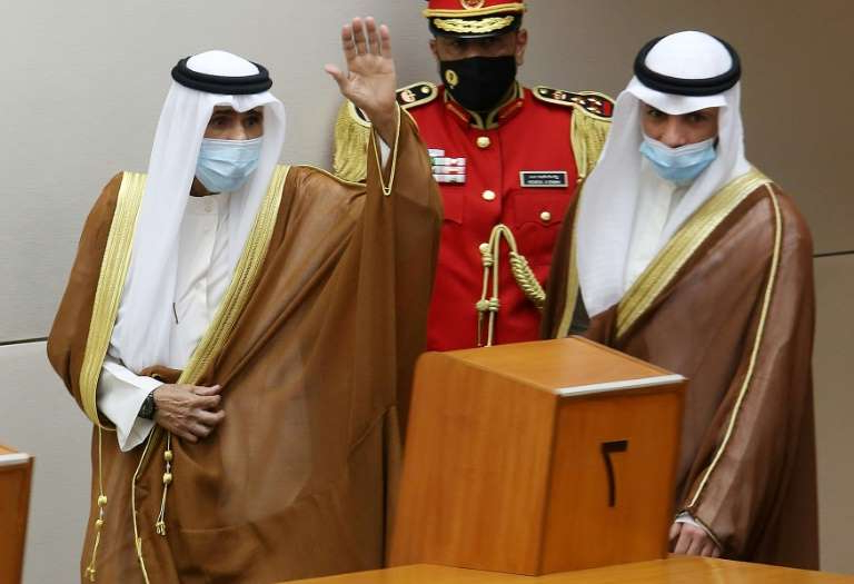a person wearing a costume: Sheikh Nawaf, right, assumes office as Kuwait wrestles with the coronavirus pandemic, which has led to a sharp decline in oil prices and severe economic repercussions for Gulf states