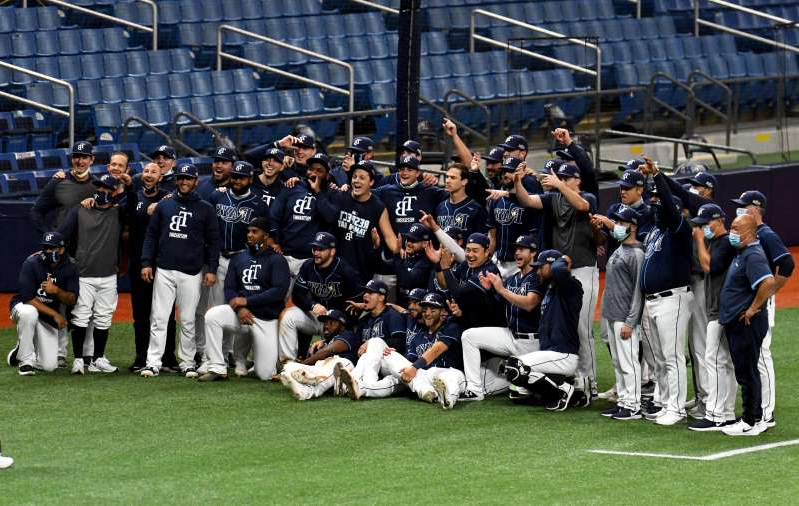 a group of baseball players playing a football game: Rays players celebrate on the field after winning Game2..