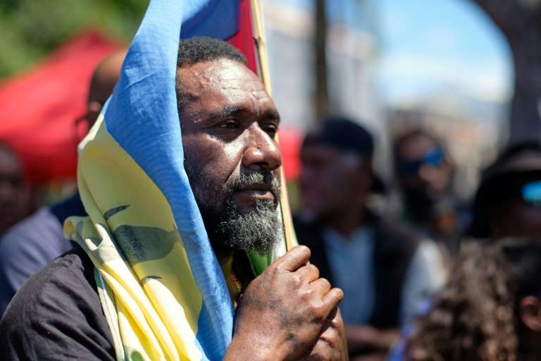 a man holding a microphone: Will New Caledonia go for independence? Observers are doubtful