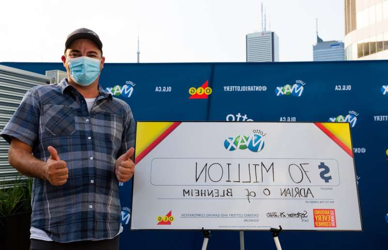a man holding a sign posing for the camera: Adrian Olmstead of Blenheim won the April 14 $70-million LOTTO MAX jackpot.