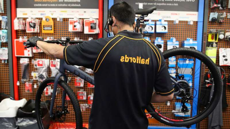 a man standing next to a bicycle: Halfords said cycling sales rose by 46%