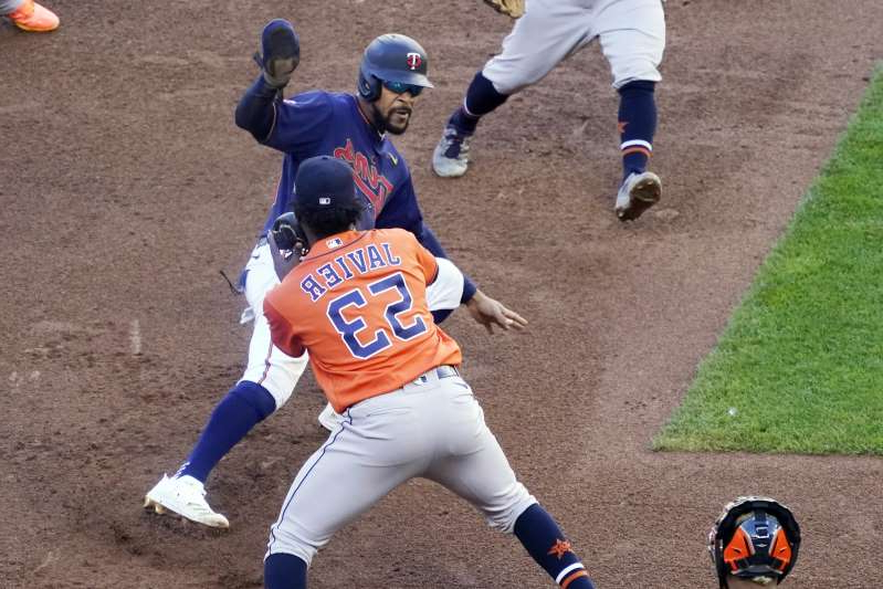 a person playing a game of baseball: Astros pitcher Cristian Javier tags out Byron Buxton during an eighth inning rundown that proved crucial in sweeping the Twins (AP Photo/Jim Mone)