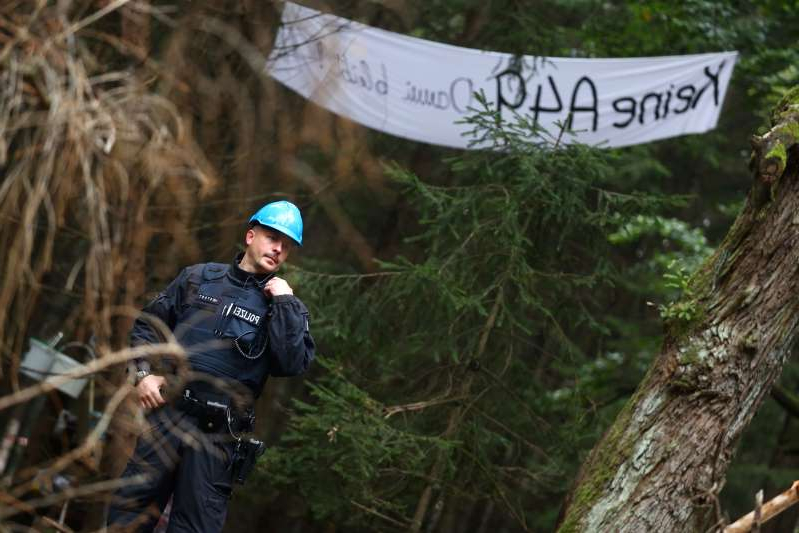 a person standing next to a forest: Protest against the expansion of the A49 motorway in a forest near Stadtallendorf