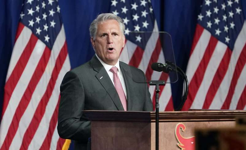 Kevin McCarthy wearing a suit and tie in front of a flag