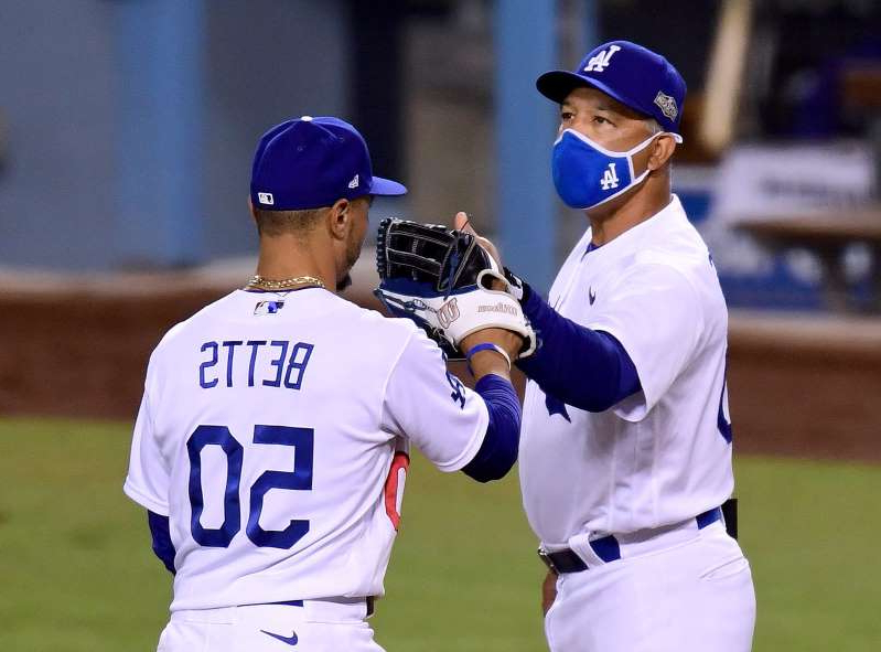 a baseball player holding a bat on a field: Dodgers manager Dave Roberts and outfielder Mookie Betts celebrate after the Game 1 win.