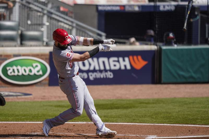 a baseball player swinging a bat at a ball: Cincinnati Reds left fielder Jesse Winker loses his bat against the Atlanta Braves during the second inning at Truist Park.