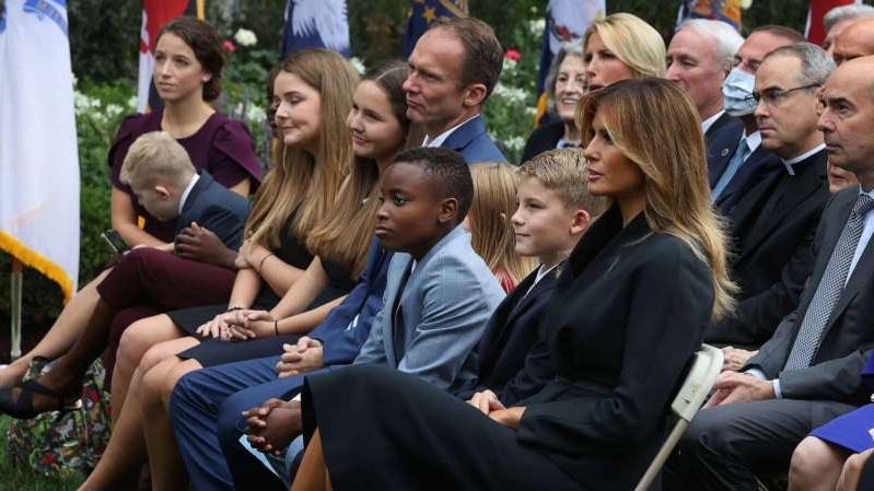 a group of people sitting on a bench: First lady Melania Trump sits next to Seventh Circuit Court Judge Amy Coney Barrett's family as President Donald Trump announces Barrett's nomination to the Supreme Court in the Rose Garden at the White House, Sept. 26, 2020, in Washington.