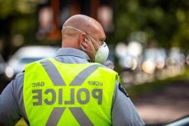 a man wearing a hat: A clean-shaven RCMP officer is pictured wearing a respirator mask and directing traffic at a COVID-19 testing centre in Burnaby, B.C., on Aug. 12. RCMP policy required front line officers to wear properly fitted N95 respirator masks — something that isn't always possible for Mounties who leave their facial hair unshorn for religious reasons.