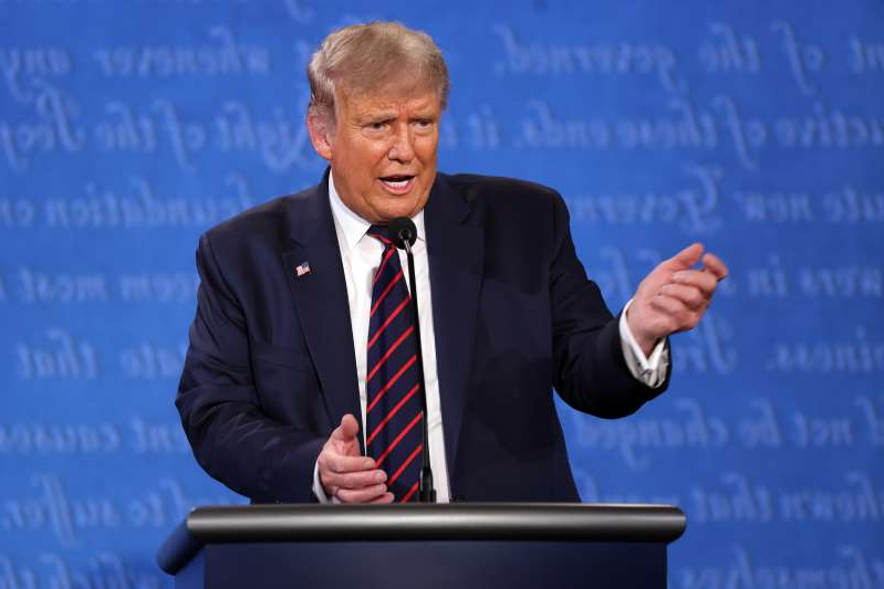 Donald Trump wearing a suit and tie: President Donald Trump speaks during the first 2020 presidential debate on September 29 in Cleveland, Ohio. New polling data shows most voters believe moderators should have the ability to mute candidates' microphones during future events.
