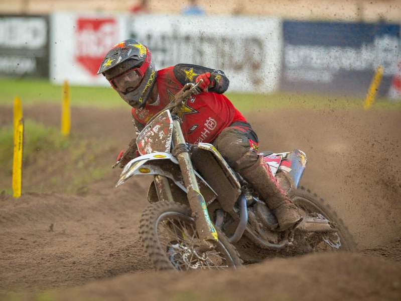 a man riding a motorcycle down a dirt road: Rockstar Energy Husqvarna Factory Racing's Zach Osborne won both motos and extended his championship point lead at round 7 of the Lucas Oil AMA Pro Motocross series.