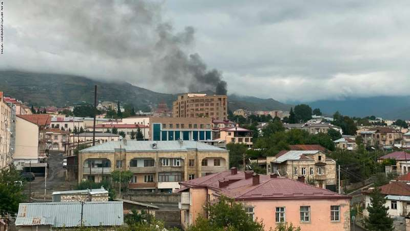 a building with a mountain in the background: Smoke rises after the recent shelling, in Stepanakert, Nagorno-Karabakh.