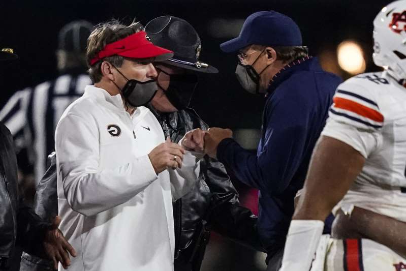 a man wearing a hat: Auburn Tigers head coach Gus Malzahn (left) and Georgia counterpart Kirby Smart bump fists at midfield after Saturday night's game at Sanford Stadium.