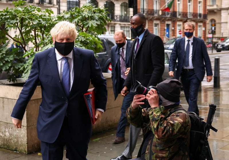 a man wearing a suit and tie walking on a sidewalk: British PM Johnson is seen outside BBC headquarters in London